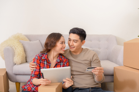 Happy asian couple doing on-line shopping with credit card Stockfoto