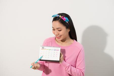 Porträt eines lächelnden jungen Mädchens, das ihre Perioden gemäß Kalender lokalisiert über weißem Hintergrund prüft