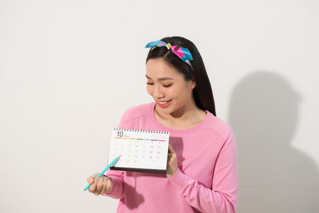 Portret uśmiechniętej młodej dziewczyny sprawdzającej miesiączki zgodnie z kalendarzem na białym tle nad białym tłem