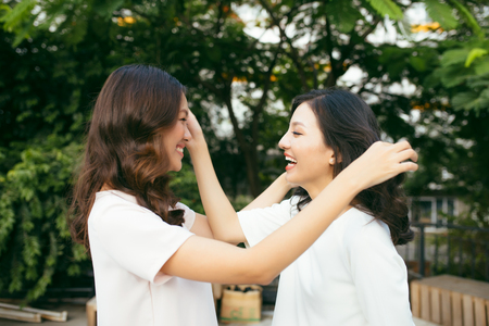 Beauties in style. Two beautiful young well-dressed women smiling at camera while standing embracing outdoors Stock Photo