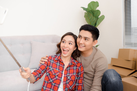 home, people, repair and real estate concept - smiling couple with big cardboard boxes moving to new place and taking smartphone selfie