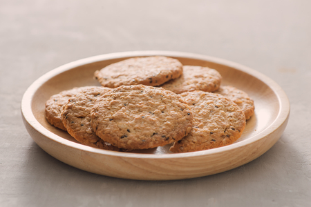 Oat cookies in plate isolated on white background, top view. Sweet bakery products. Round cookies in a wooden plate. 版權商用圖片