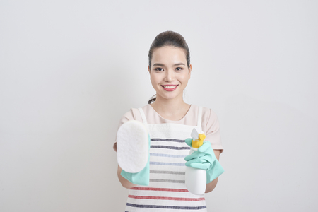 Beautiful cheerful woman holding different cleaning stuff. Isolated Stock Photo