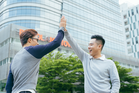 Closeup of two smiling business men high fiving with office building in background - Image