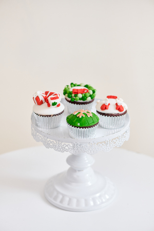 Homemade Christmas cupcake with traditional red green decorative symbols elements
