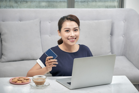 Happy asian woman lying on the floor carpet and shopping online with credit card and laptop at home. Online shopping, technology, winner and e-money concept