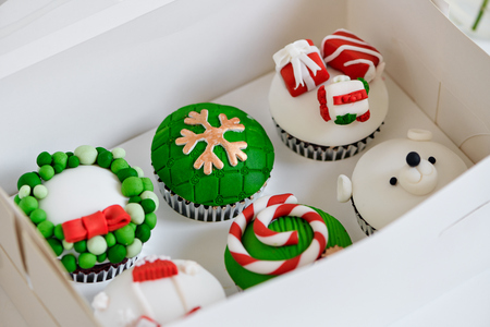 Seasonal festive christmas mini dessert cupcakes in traditional red green decorative symbols elements 免版税图像