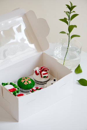 Seasonal festive christmas mini dessert cupcakes in traditional red green decorative symbols elements Stock Photo