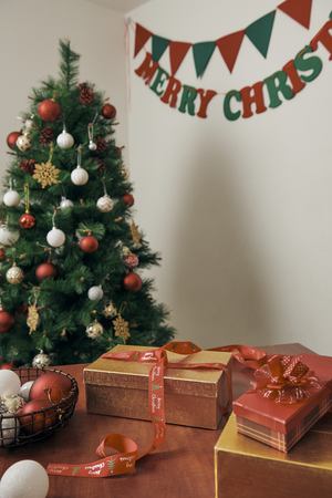 Merry Christmas and Happy New year Holidays! Decorating the Christmas tree indoors. Macro or close picture of xmas tree and gifts