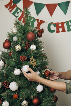 handsome man decorating christmas tree with baubles and looking at camera at hom