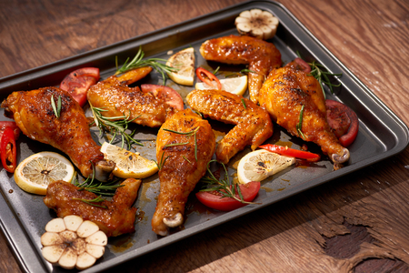 Baked chicken drumstick and wings on baking tray over dark wooden background. 스톡 콘텐츠