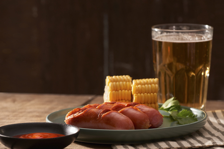 Beer and grilled sausages on wooden background Standard-Bild - 114458653