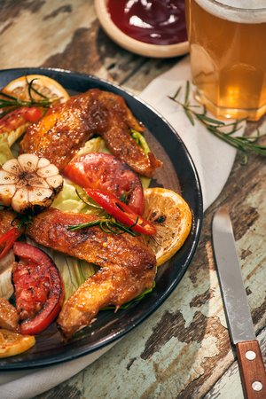 Grilled chicken wings spiced with chili peppers and rosemary