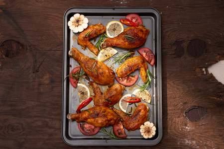 Roasted chicken wings on baking tray over dark wooden background with copy space. Top view, flat lay
