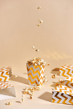 Salty fresh crusty homemade popcorn in golden paper cup in the fashion beige background in a New Years interior. selective focus