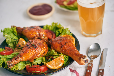 Grilled chicken legs roasted on the grill on dark plate with tomato sauce in a bowl and lettuce leaves, glass mug of beer Stock fotó