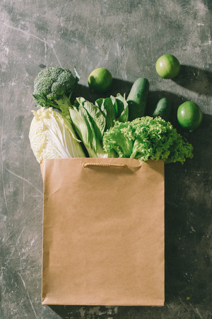top view of green vegetables in shopping bag on wooden table Stock Photo