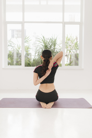 Attractive young woman stretching and warming up before workout Stockfoto