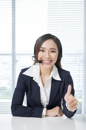 Call center operators. Young beautiful business woman in headset Stok Fotoğraf