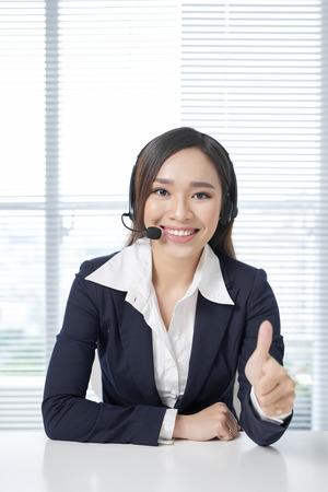 Operatorzy call center. Młoda piękna biznesowa kobieta w zestawie słuchawkowym
