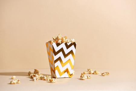 Popcorn casalingo croccante salato fresco in tazza di carta dorata nella moda sfondo beige in un interno di Capodanno Archivio Fotografico