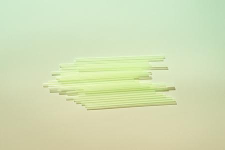 Cannucce di plastica verde su sfondo chiaro. Forniture per eventi e feste. Concetto di inquinamento della terra