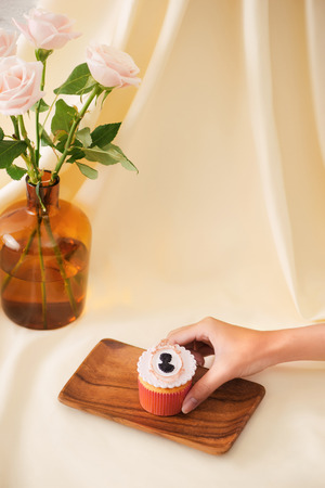 Female hands cut the delicious cupcakes on table Stock Photo