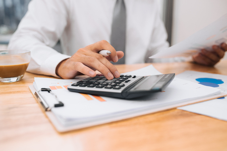 Partial view of businessman with calculator working at workplace with documents and laptop