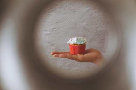 Valentine sweet love cupcake in hand on light background Stock Photo