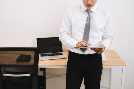 Unknown businessman holding digital tablet in office Фото со стока