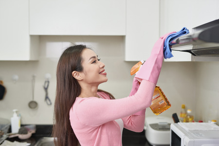 Woman in protective gloves cleaning kitchen with rag, indoors Stock Photo