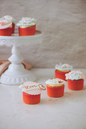 Cupcakes decorated with fondant. Valentine sweet love cupcake on table on light background Stock Photo