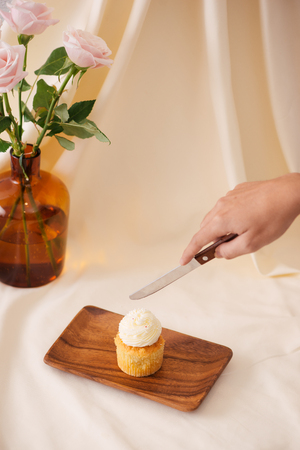Female hands cut the delicious cupcakes on table 版權商用圖片