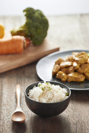 White rice with curry and chicken in black plate on wooden table