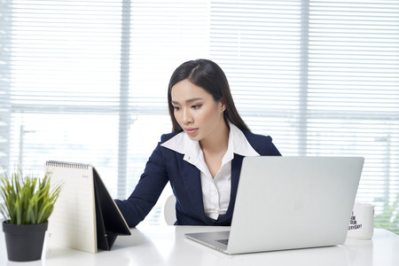 Confident asian businesswoman sitting by desk with laptop in office