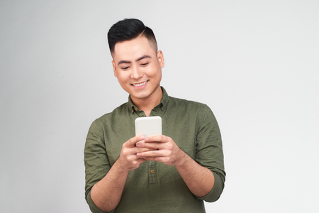 Happy man in glasses typing sms on gray background Stock Photo