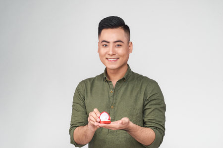 Asian man gives a ring with a diamond in a red box