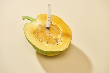 Bright ripe papaya fruit with syringe extracting liquid and showing concept of cellulite treatment Stock Photo