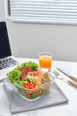 Geschäftsfrau, die organische vegane Mahlzeiten von der Lunchbox zum Mitnehmen am Arbeitstisch mit Laptop isst? Standard-Bild