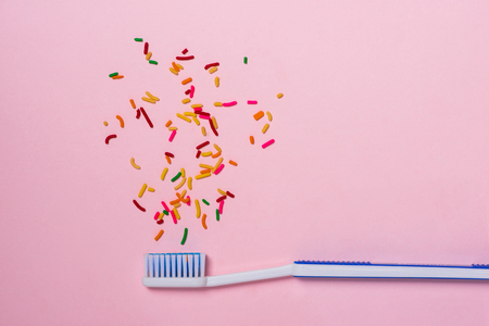 Toothbrush and candy on the pink table. Candy causes tooth decay. Dental Care Concept. Banco de Imagens