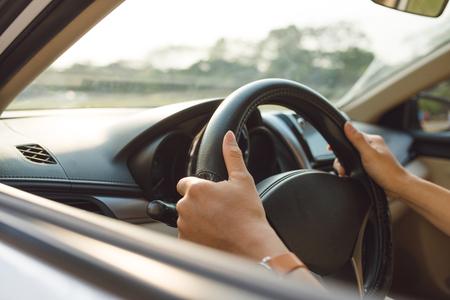mani maschili sul volante a destra con vista lato campagna
