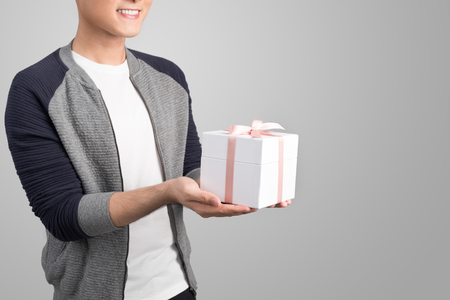 Theme holidays and gifts: a man holds an exclusive gift in a white box wrapped with pink ribbon and bow isolated on a gray background in studio