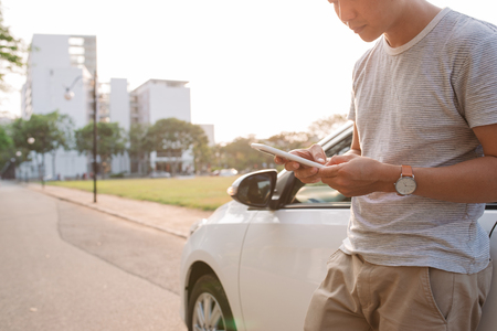 Young man is standing near the electric car and looks at the smart phone. The rental car is charging at the charging station for electric vehicles. Car sharing.