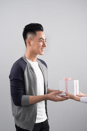 Happy smiling couple in love standing over gray background. Standard-Bild - 115228731