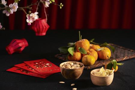 Imagen conceptual del año nuevo lunar: mandarina, mermelada y paquete rojo. El texto en el sobre significa Feliz Año Nuevo y Felicidad.