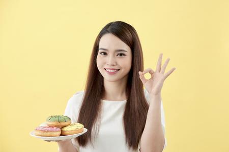 若い女性は指でOKサインをやってプレートドーナツを持って、優れたシンボル