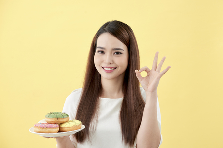 Young woman holding plate donut doing ok sign with fingers, excellent symbol