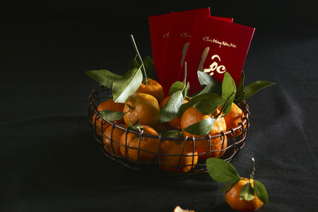 Red envelopes, gold envelopes and Tangerine and mandarin orange for Lunar New Year. Text on envelop means Happy New Year and Happiness.