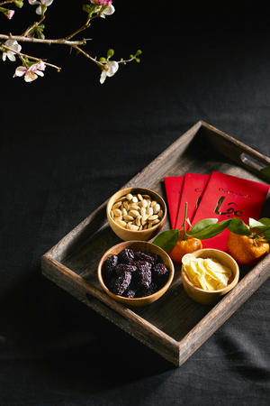 Group of colorful Vietnamese jam for Vietnam Tet holiday, also lunar new year of Asia, traditional preserved fruit from jujube, ginger jam and pumpkin seeds, tangerine. Text on envelop means Happy New Year and Happiness.