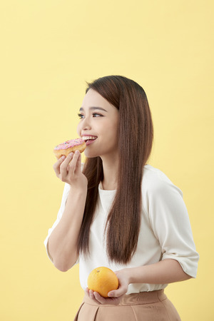Dieting concept. Beautiful Young Asian Woman holding orange and donut over yellow background. Choosing between junk food with healthy food. Stockfoto